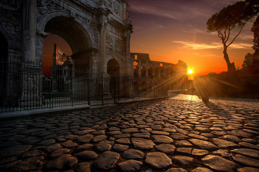 A cobblestone road leading up to the Colosseum in Rome at sunset.