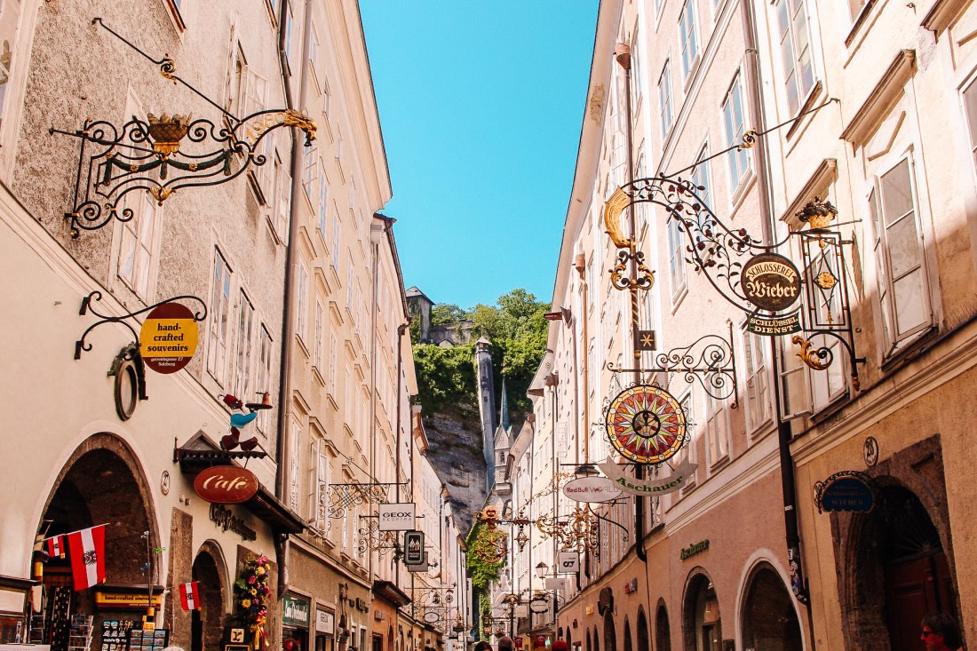 The wrought-iron signs hanging from the buildings of Salzburg's Getreidsgasse. A cliff and a tower rises up in the background.