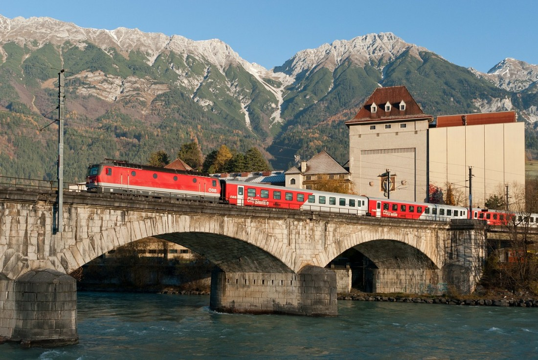 A train goes over a bridge in front of the mountains. When on a Vienna to Salzburg day trip, the train is often the best option for travel.