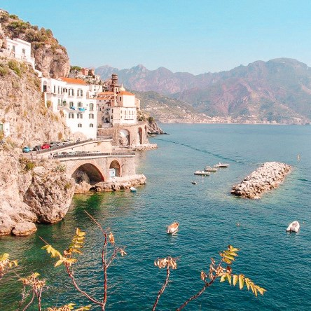 The small town of Atrani near Amalfi, with blue seas and small boats off its coast.