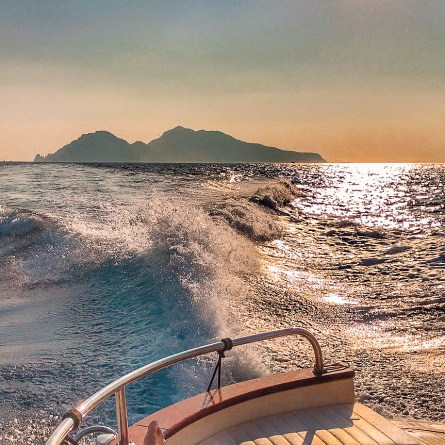 The view from a boat looking back at Capri, whilst the sun sets.