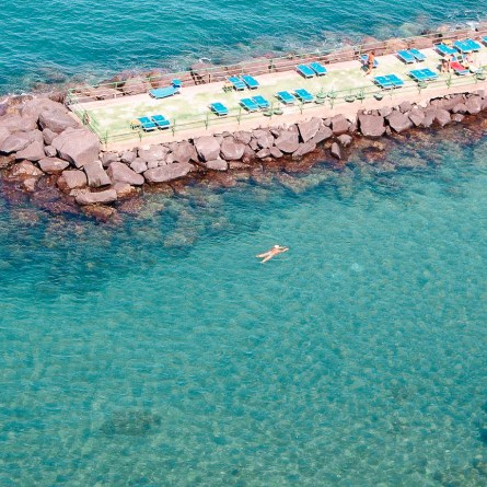 Leonelli's Beach, one of the most instagrammable spots on the Amalfi Coast. A person swims though blue waters near a lido with sunbeds.