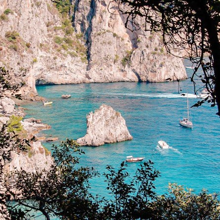A view of Capri's Via del Pizzolungo. A rock rises out of blue waters, surrounded by pine trees. One of the most Instagrammable places in Capri.