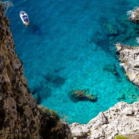 Capri's Via Krupp, definitely one of the most instagrammable spots on the Amalfi Coast. A speedboat sits in crystal blue waters near white rocks.