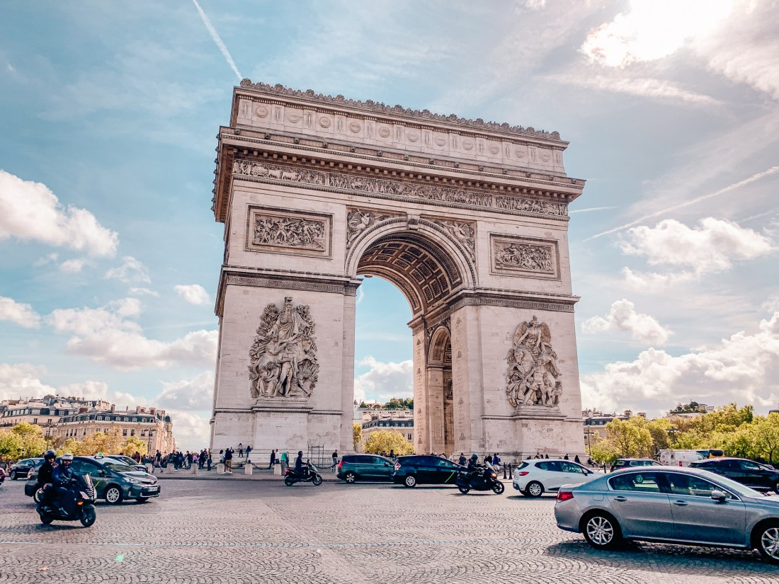 The Arc de Triomphe in Paris, with cars driving below it. A must if visiting Paris for the first time!
