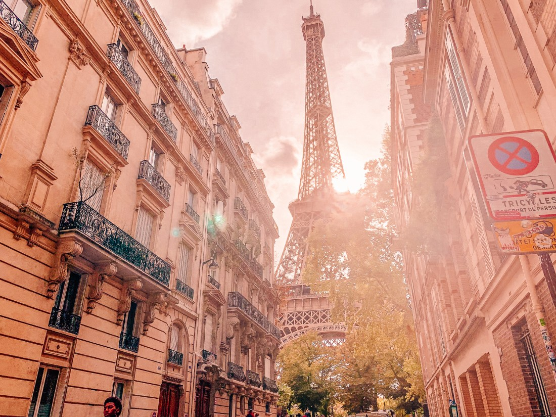 The Eiffel Tower, the most famous of all Paris landmarks, seen between two buildings
