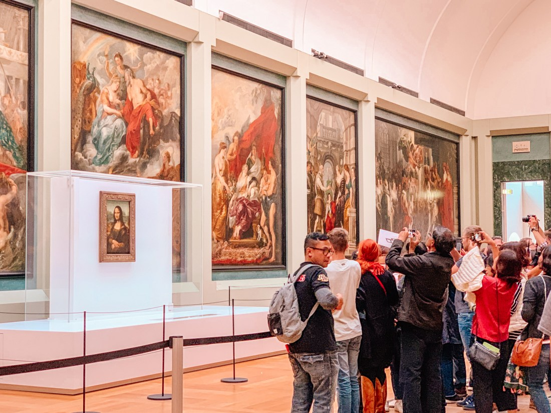 A group of people photograph the Mona Lisa in the Richelieu Wing of the Louvre. Large paintings provide a backdrop on the walls.
