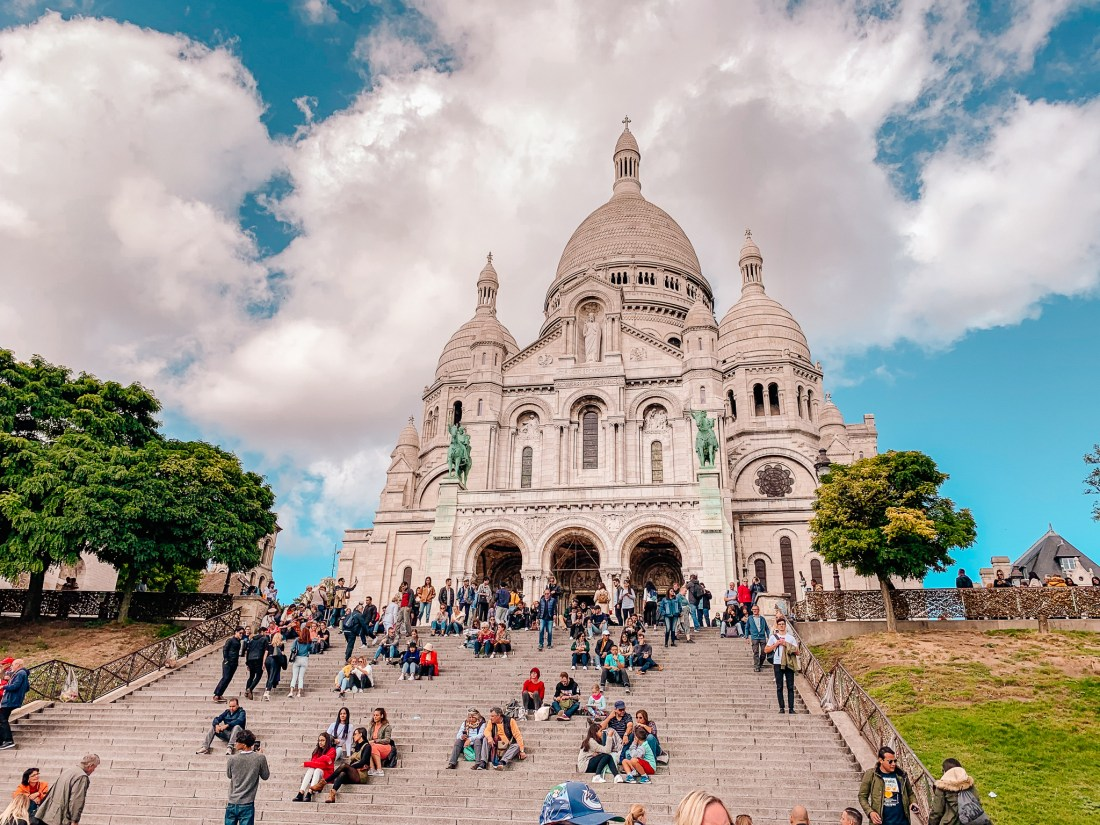 The church of Sacre Coeur in Paris's Montmartre district. A staircase leads up to the church, with people sitting on it. The church has a large dome on top.