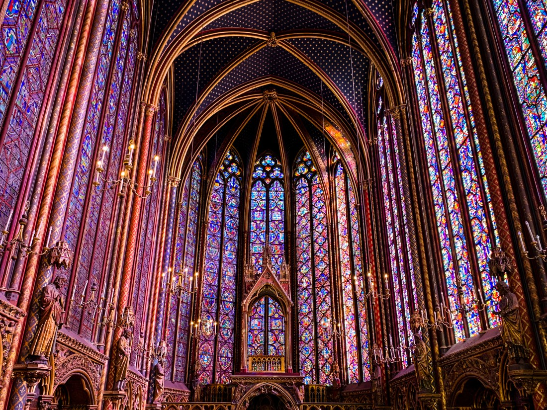The inside of Sainte Chapelle church, with all four walls covered in stained glass.