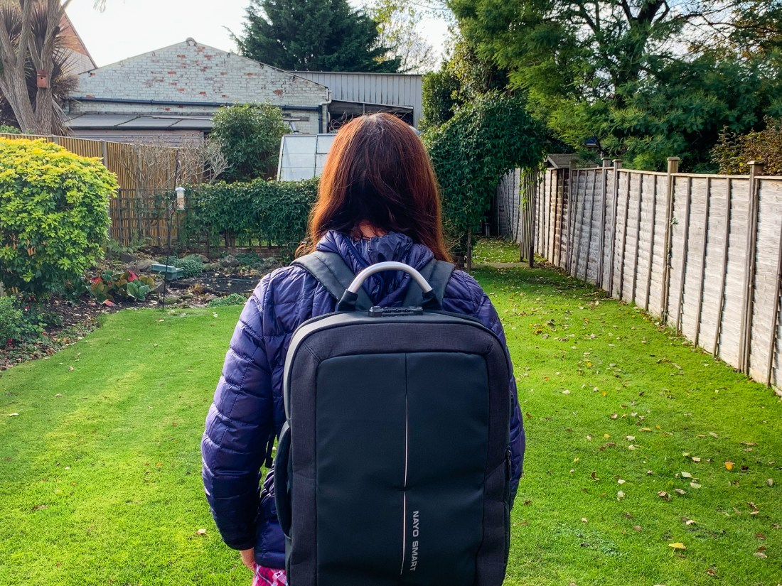 A woman wears the Nayosmart anti theft backpack in a garden