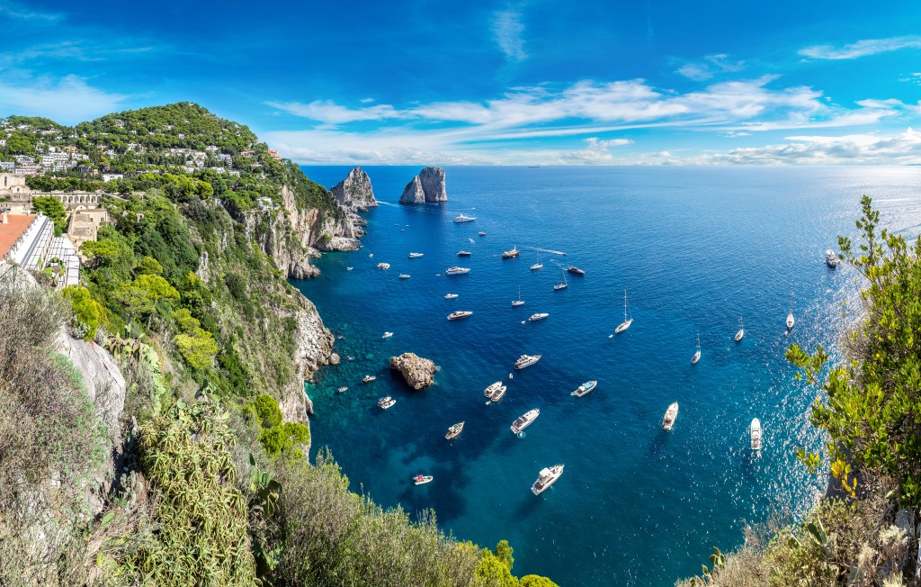 Boats sit on the sea near Capri. Capri is one of the best places to stay in the Amalfi Coast