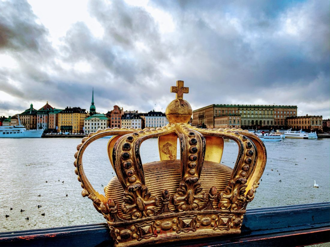 A golden crown on a bridge, in front of a watery harbor and a view of Gamla Stan in Stockholm, Sweden