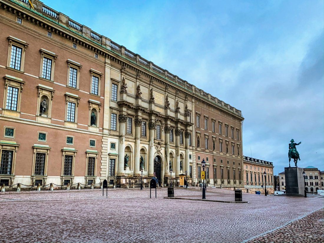 The outside of Stockholm's Royal Palace, a rose/cream/brown colored building with a guard outside.