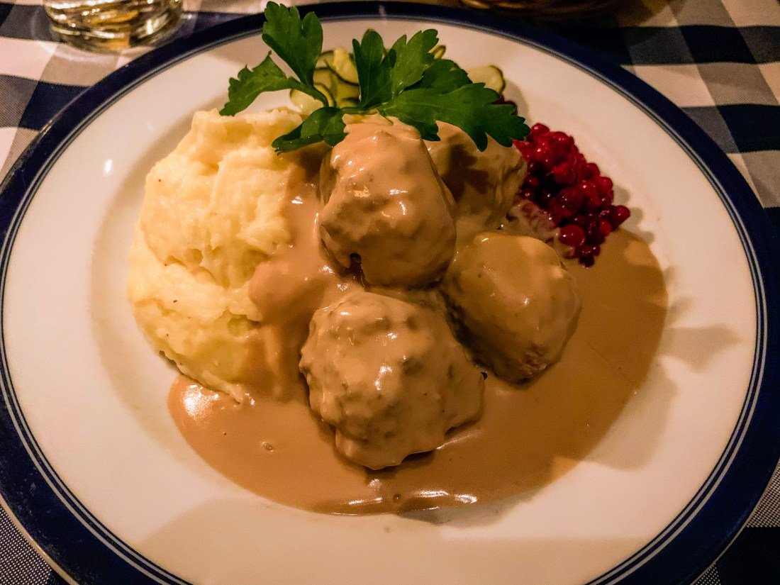 A plate of elk meatballs with potato and lingonberry at Bla Dorren in Stockholm