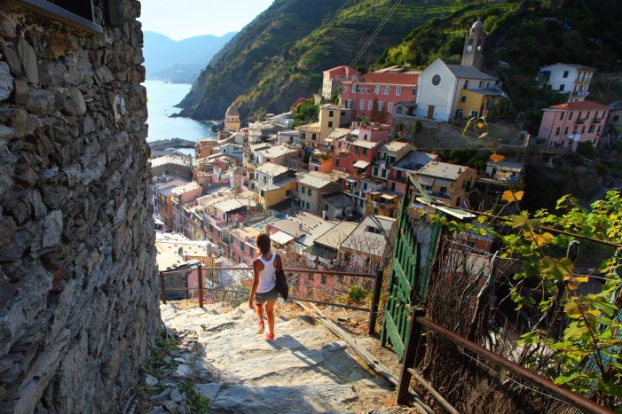 A woman visiting Italy and taking a walk through Cinque Terre. Seeing the sights is still possible on a virtual tour of Italy