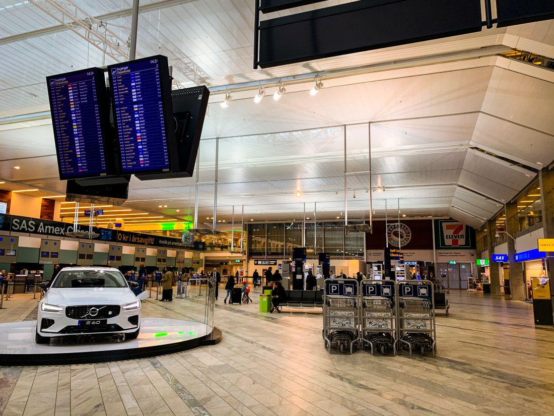 The interior of Gothenburg Airport, with a white car on show. This is the starting point for going from Gothenburg Airport to cit center