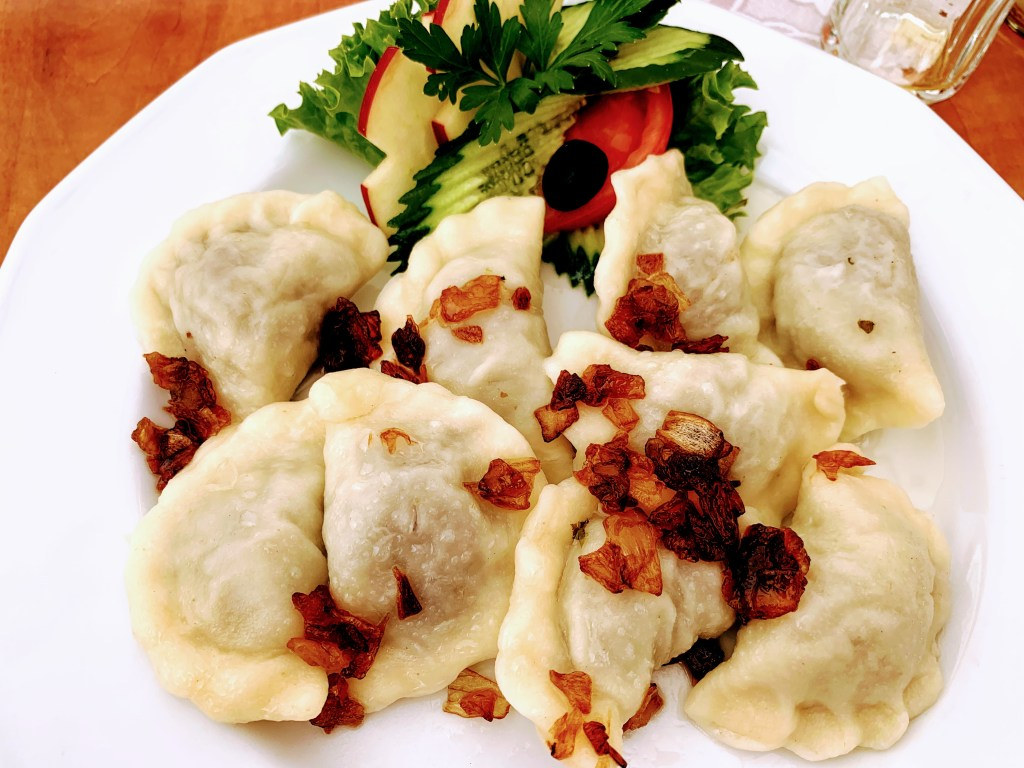 A plate of Polish filled dumplings (pierogi) with a salad garnish