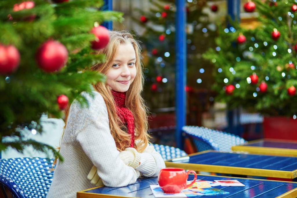 A young woman sits outside a cafe in Paris at Christmas
