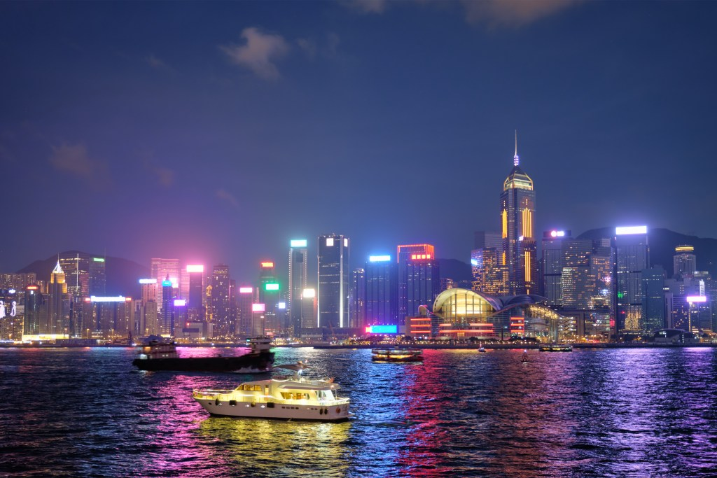 A view of the Hong Kong skyline at night, with colourful lights reflecting on to the water