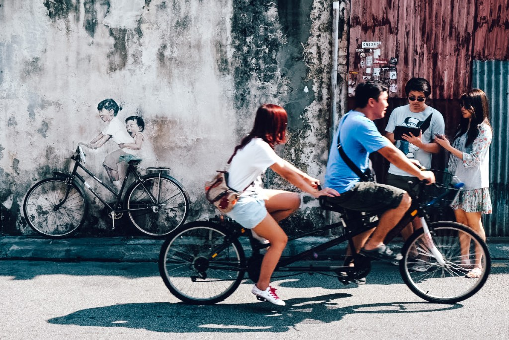 A man and woman cycle past street art in Penang, Malaysia.
