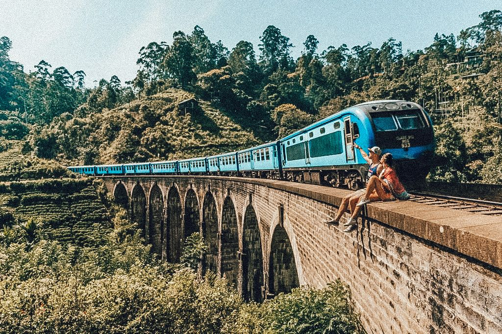 A train goes past a young couple in Kandy, Sri Lanka