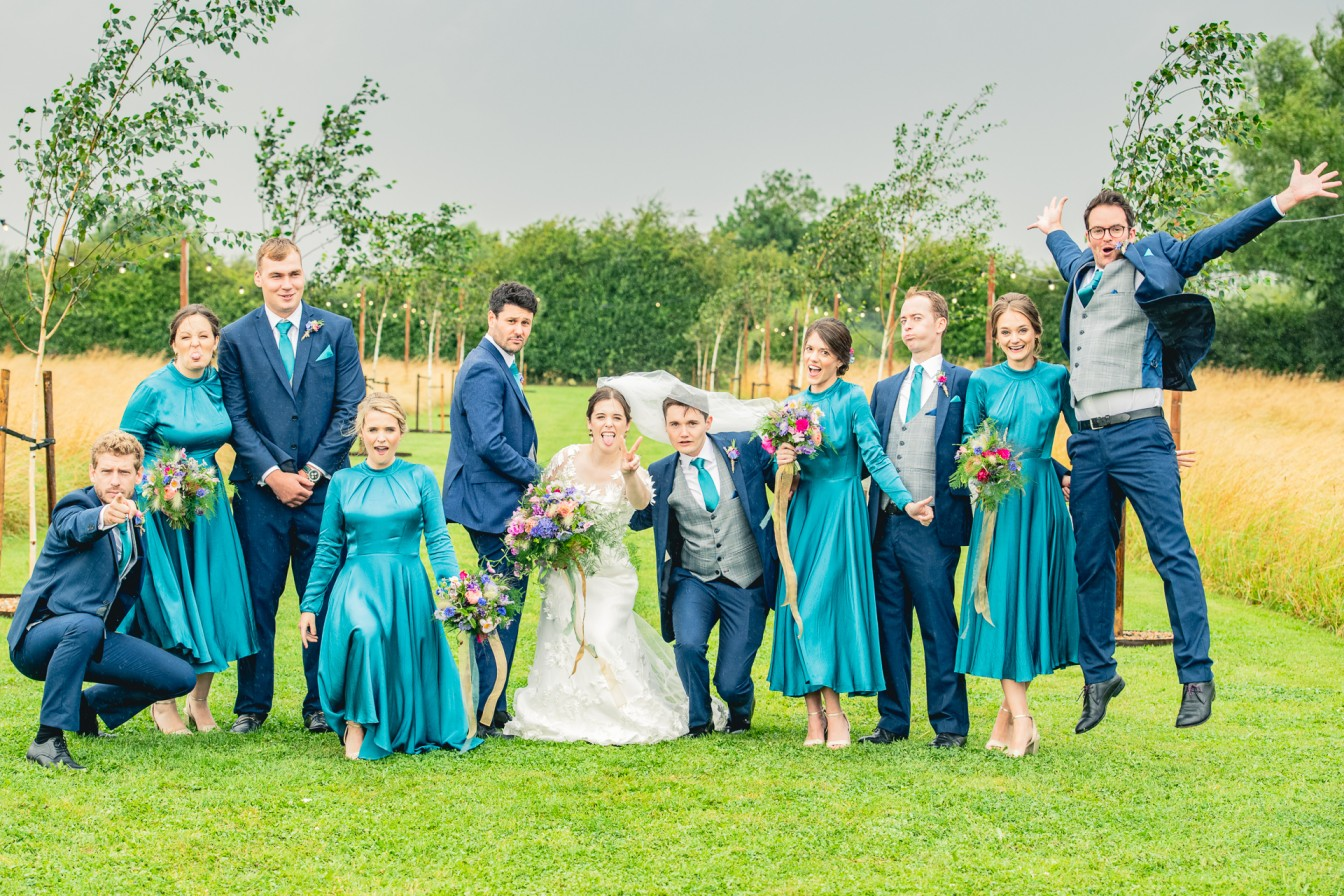 B&A wedding day - Oaktree farm outdoor wedding venue in nottinghamshire / lincolnshire - bridal party group shot in the rain - teal bridesmaid dresses