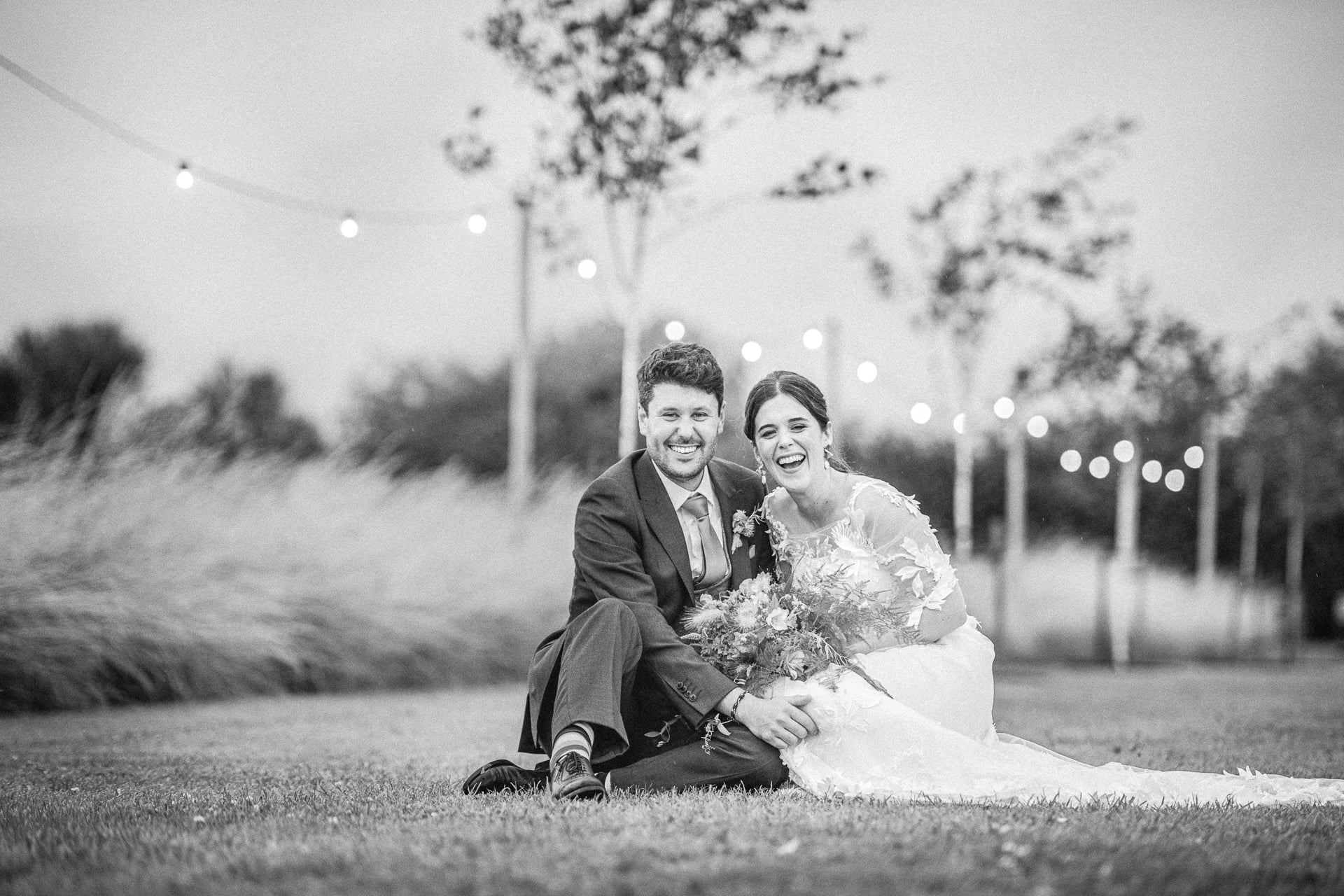 B&A wedding day - Oaktree farm outdoor wedding venue in nottinghamshire / lincolnshire - couple sitting on the grass laughing