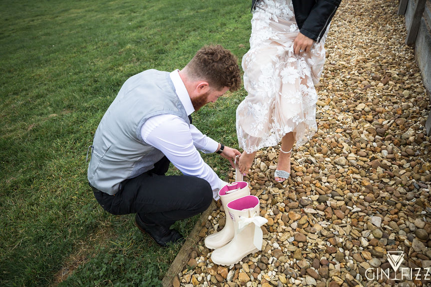 B&N outdoor wedding day - groom putting bridal wellies onto brides feet