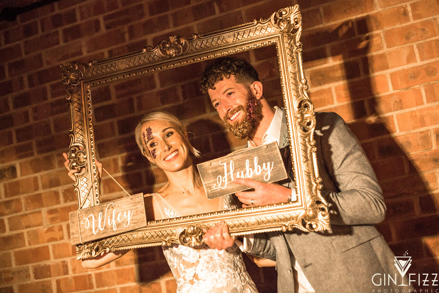 B&N wedding day castle view farm and stables old school photobooth hubby and wifey with large gold frame smiling with glitter 4