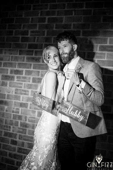 B&N wedding day castle view farm and stables farm leicestershire barn wedding venue - photobooth picture of bride and groom holding wifey and hubby signs 2