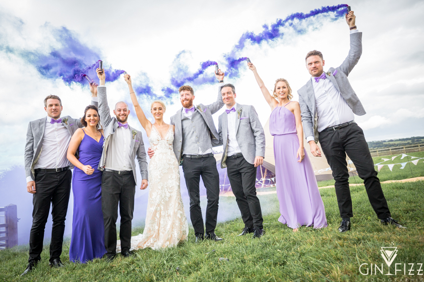 B&N wedding day castle view farm and stables farm leicestershire barn wedding venue - bridal party holding purple smokebombs in front of tipi