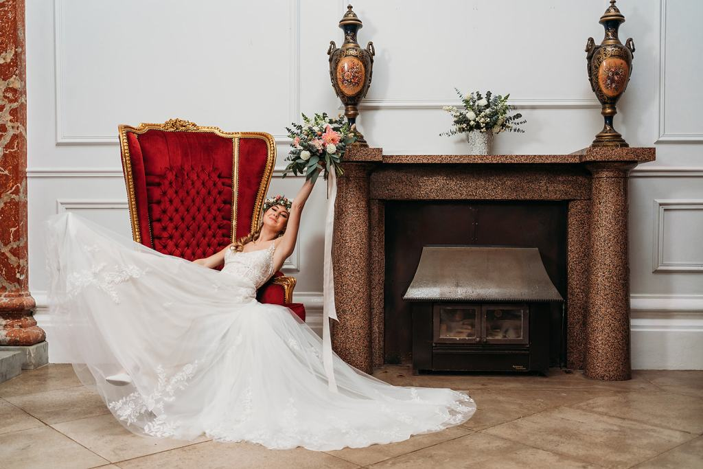 Warwickshire wedding venue - wedding ceremonies at Fillongley Hall - Entrance Hall fireplace with Bride in Chair with Bouquet 2