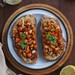 Chickpea Tahini Toast on a white plate over a wooden surface