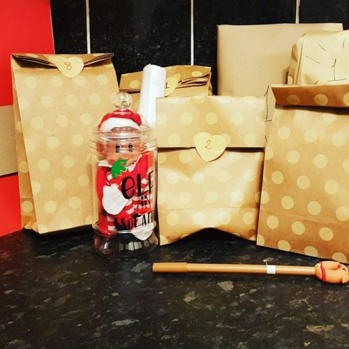 Elf on a shelf surrounded by parcels