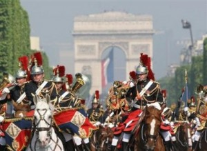 mounted military figures parade for Bastille Day with Arc de Triomphe in the background.