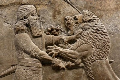 Ashurbanipal chokes a lion with his bare hand and stabs it with a sword. Assyrian Frieze British Museum 600's BC