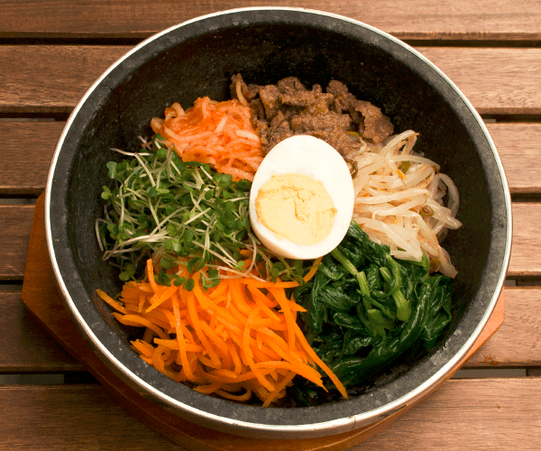 stone bowl of korean bibimbap with egg, carrots, spinach, cress and beansprouts