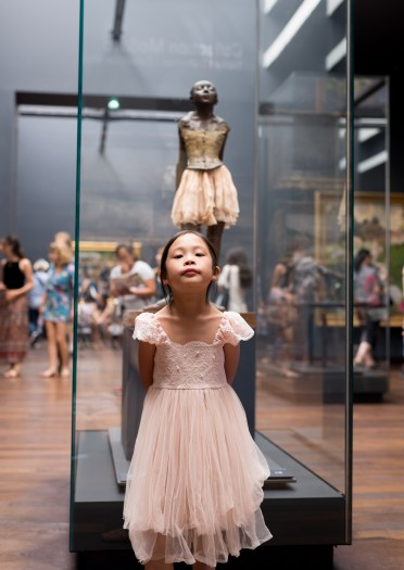 Young girl posing as Degas's ballet dancer sculpture at musee d'orsay