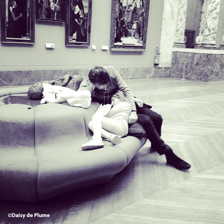 child asleep on adults lap on seat in centre of an art gallery
