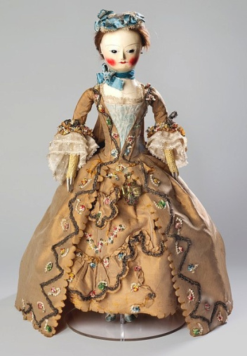 18th Century French Pandora fashion doll wearing gold dress with colourful details and with a creepy face