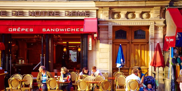 Sunny paris street cafe under red awnings
