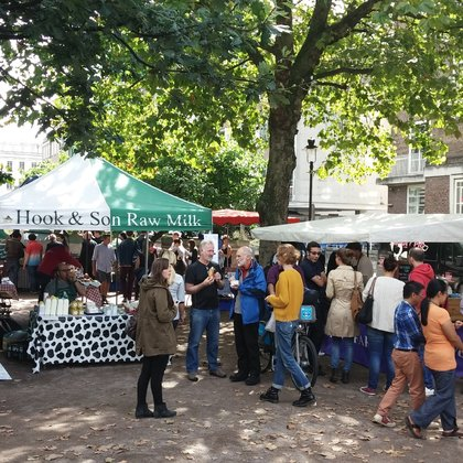 Shoppers stood by local milk stall under a tree at bloomsbury market