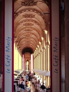 Diners at Le cafe marly, sat underneath sunny arched terrace between cafe banners