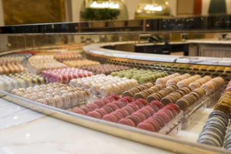 multicoloured macarons arranged in a glass display case