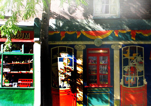 colourful painted facade of Pollock's Toy Museum with windows full d vintage toys