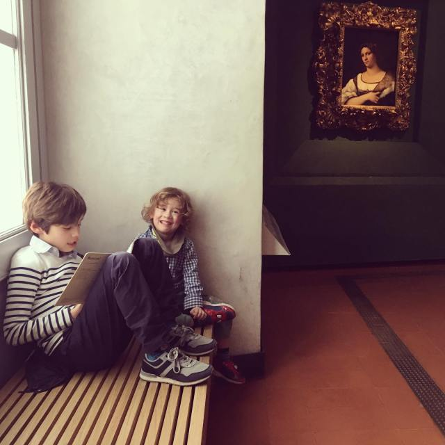 two boys sitting on a museum bench