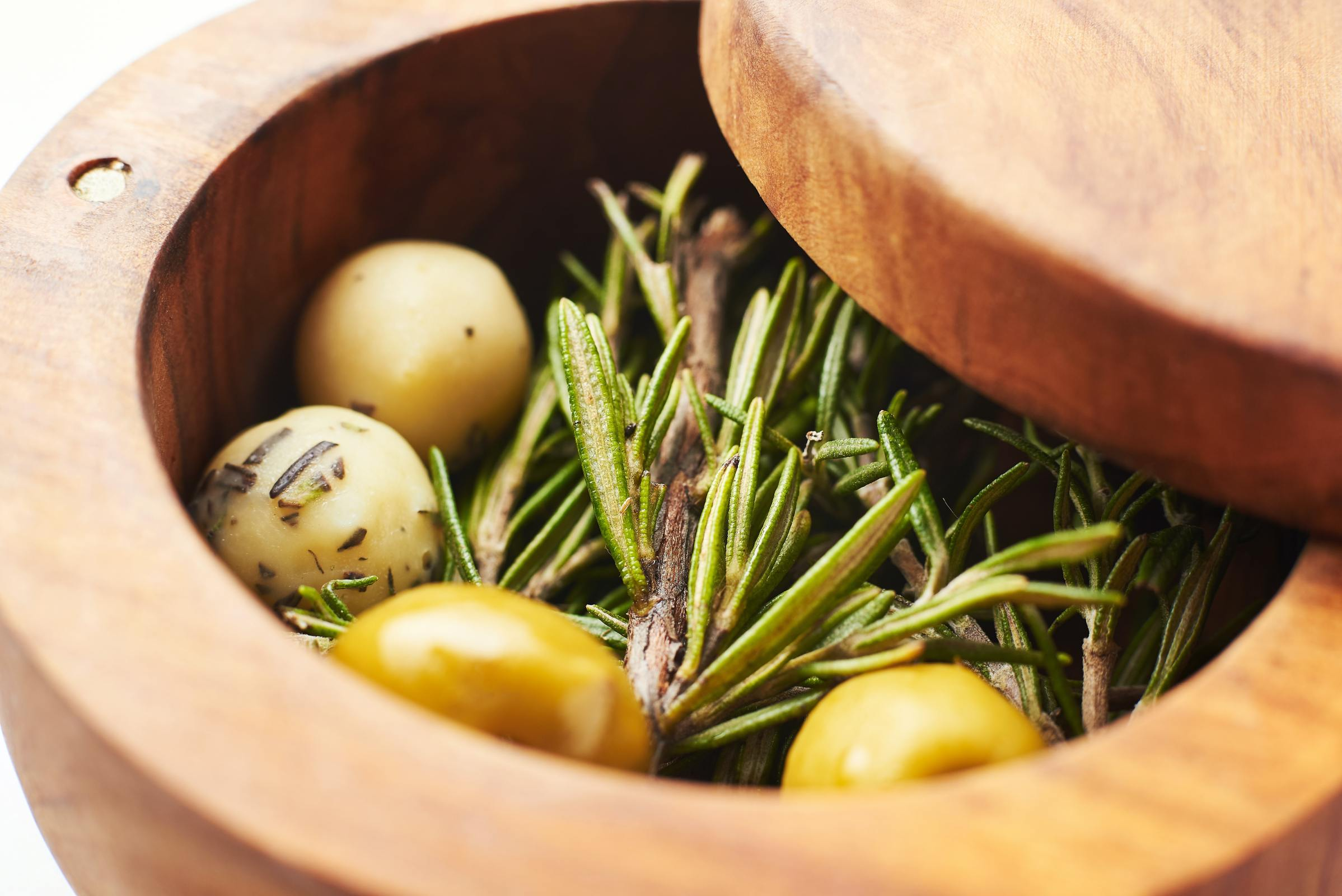 Olives and herbs in a wooden bowl