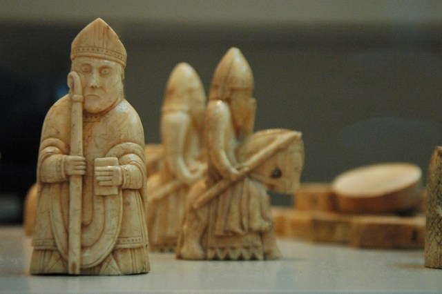 Image of the Lewis Chessmen at the British Museum: three small chess figures carved from ivory.