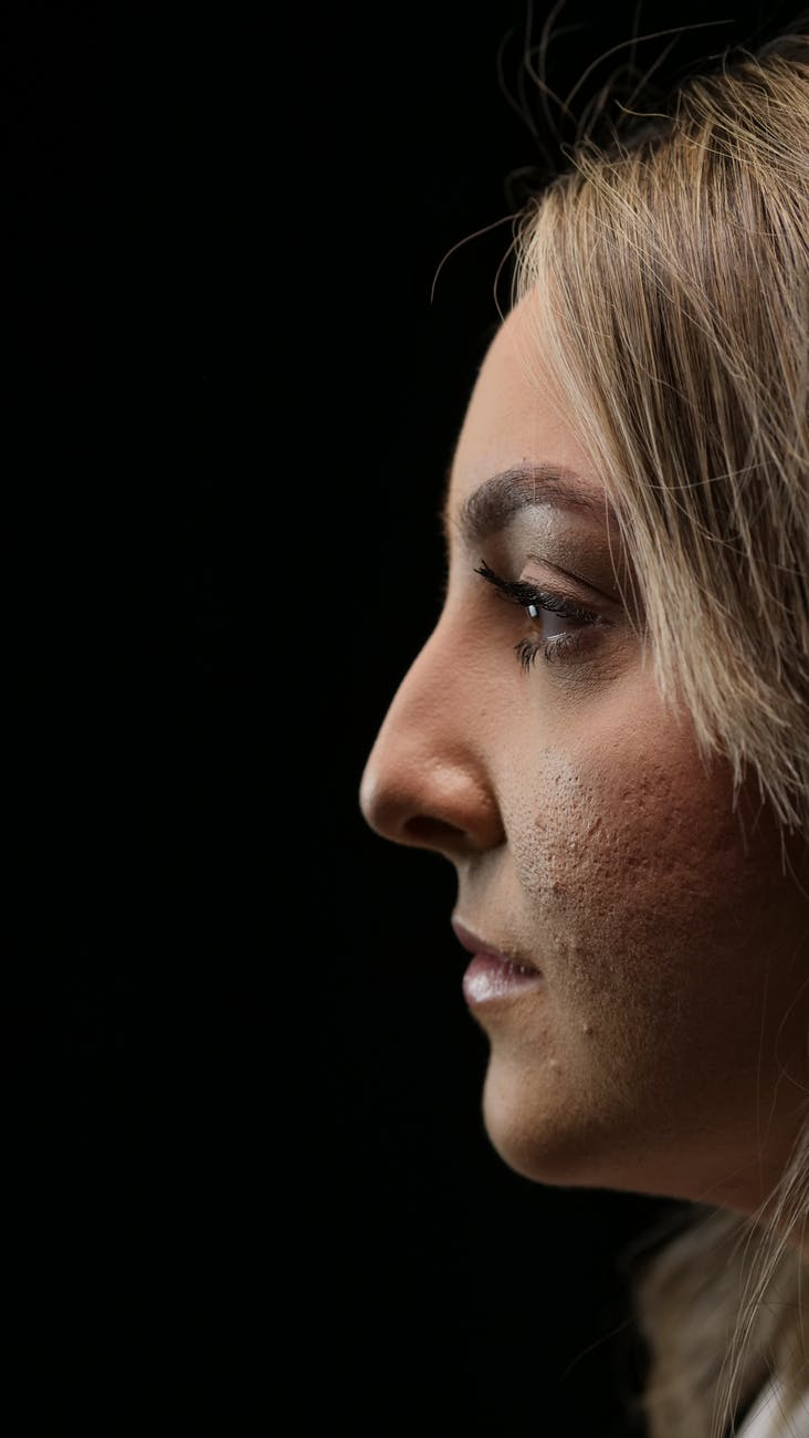 side profile of woman in black background