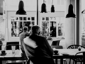 the back of a man sitting in a cafe with coffee cups around him